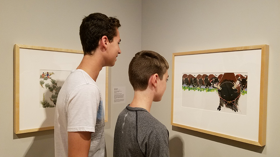 "2 boys viewing Paul Goble illustration in ""Heroes, Saviors and Triumphs"" exhibit."