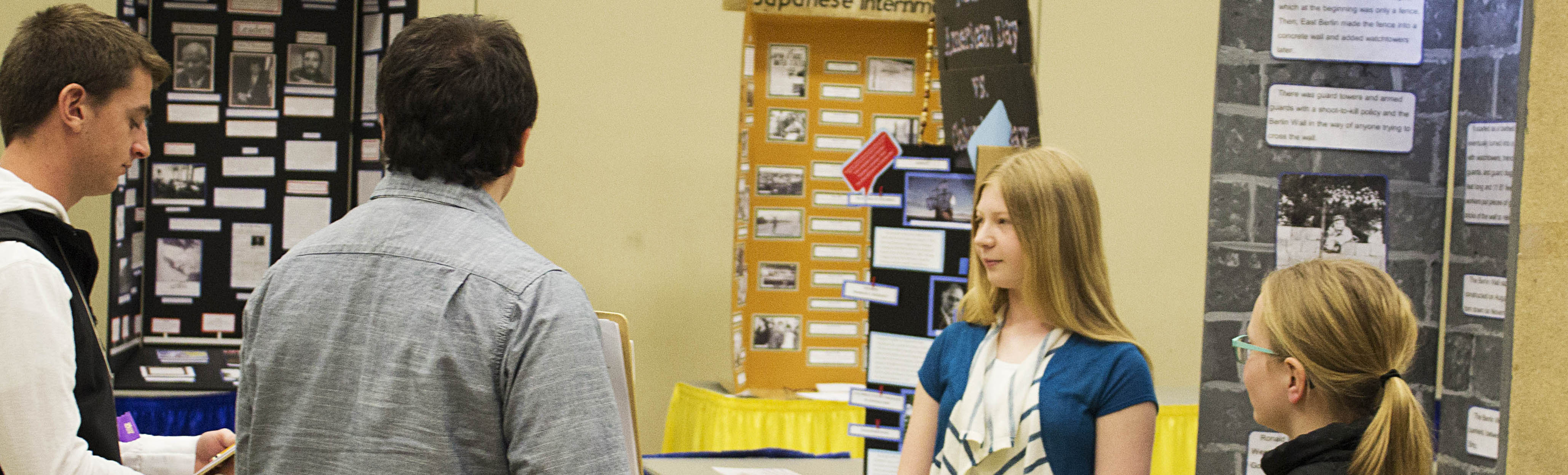 Two NHD in SD Judges interviewing two female students about their exhibit.