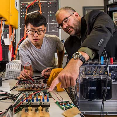 student and professor in electronics lab