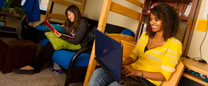 A student works on a laptop while two other students study in a residence hall.