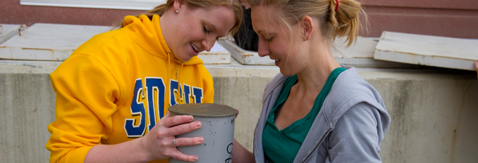 Two students work with cement.
