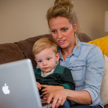 Mother with her toddler son on their couch working on a computer