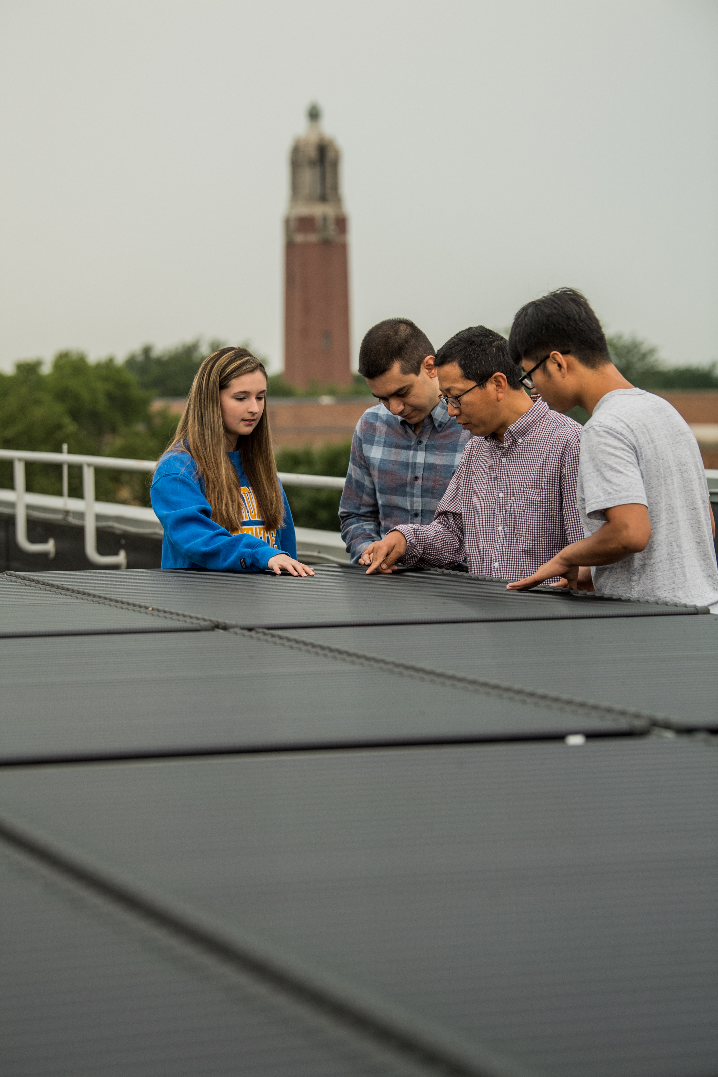 Students researching solar panels with professors
