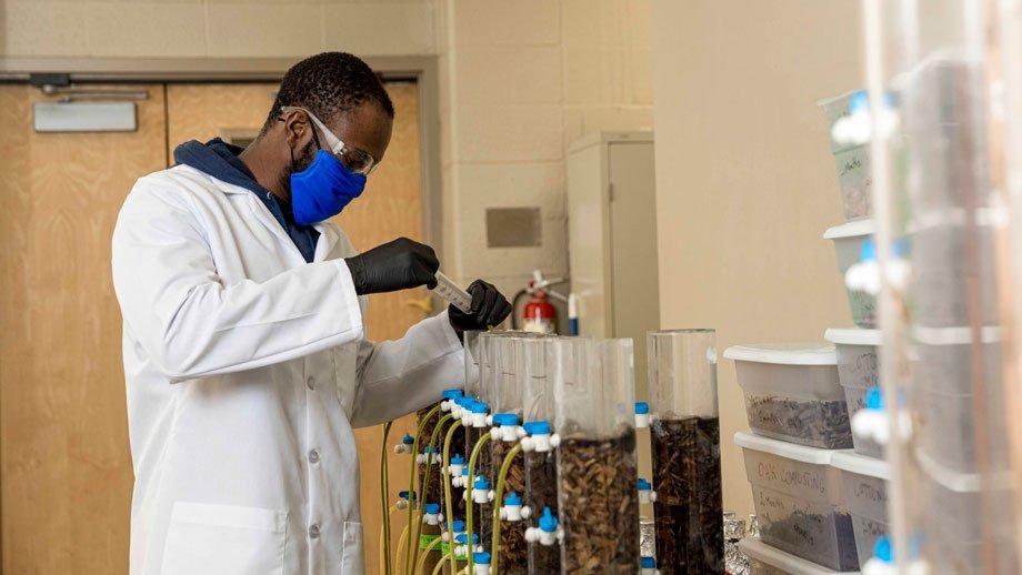 Abdoul Kouanda taking water sample from column reactor