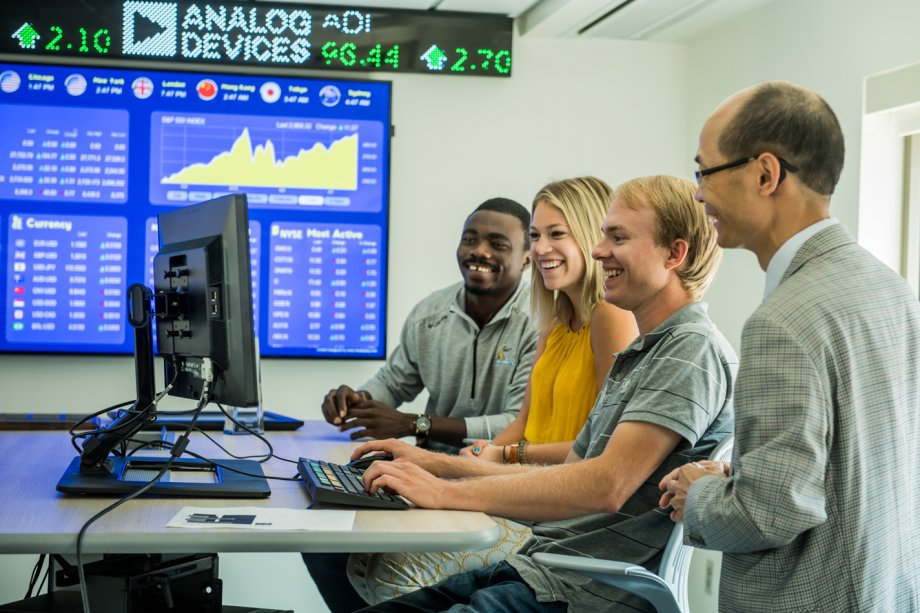 Three students and professor viewing a computer screen