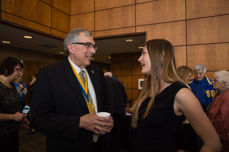 Barry H. Dunn visits with Allyson Helms, SDSU Student Association President after the announcement