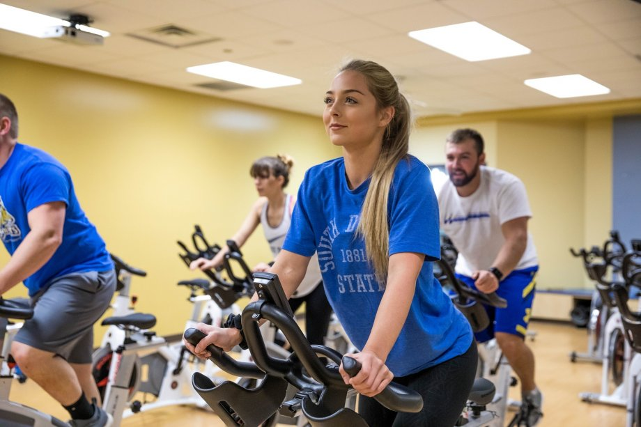 Students work out on exercise bikes in the Wellness Center.