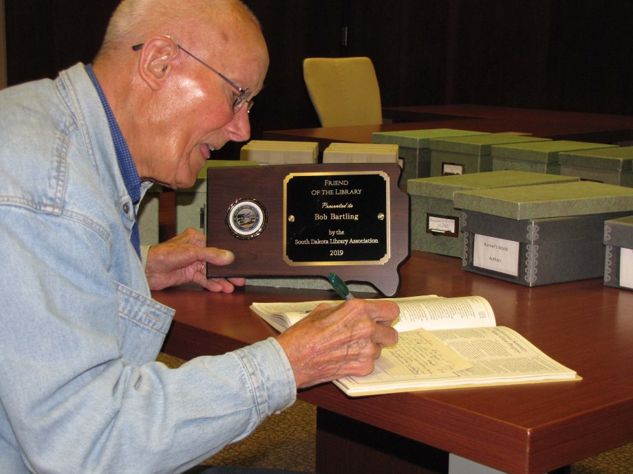 Bob Bartling, 93, of Brookings, makes an entry in his index card system while working at Briggs Library Sept. 30. As the plaque shows, he was named South Dakota Friend of Library at the South Dakota Library Association's conference Sept. 26.