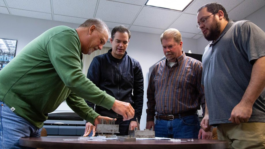 Chris Peterson, Brian Logue, Mike Peterson and Randy Jackson examining parts and mold for cyanide detector