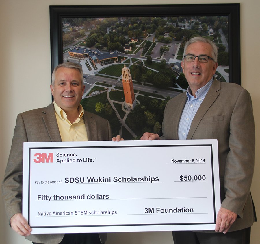 Dale Tidemann, left, plant manager of 3M Brookings, presents a check for $50,000 to SDSU President Barry Dunn