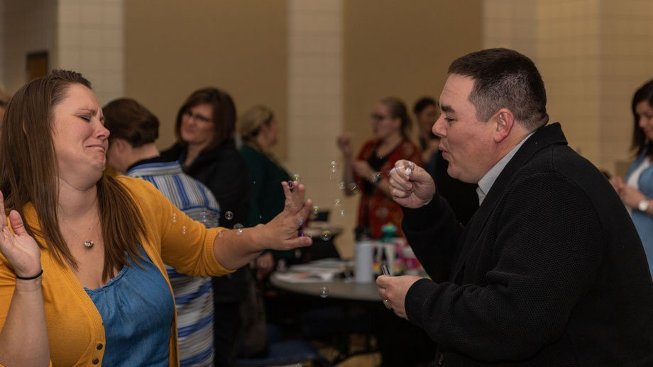 Two school counselors participating in bubble-blowing activity at workshop