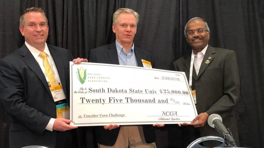 Muthu, far right, holding a huge check with two people from the Corn Grower's Association