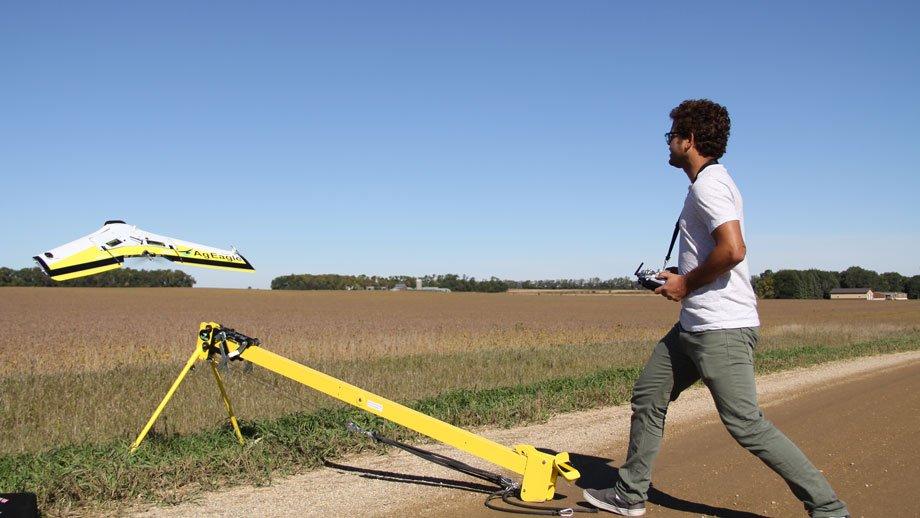 man launching drone across a soybean field