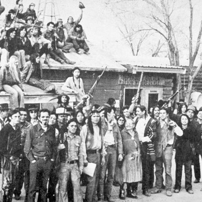 "Native American activists during the Wounded Knee Occupation. A sign above the door in the background reads ""Independent Oglala Nation Wounded Knee."""