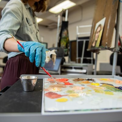Student painting in a studio.