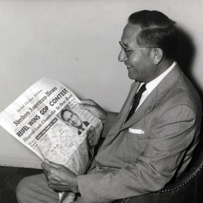 Ben Reifel reading an Aberdeen American News newspaper heading declaring him as the winner of the 1960 Republican primary