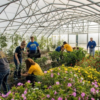 Students and instructor working in a greenhouse.