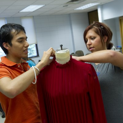 Two students hemming sweater on mannequin.