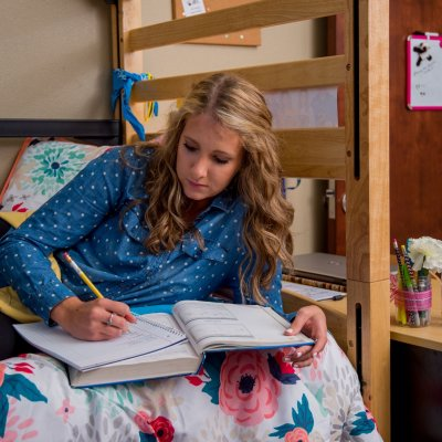 Student studying on her bed.