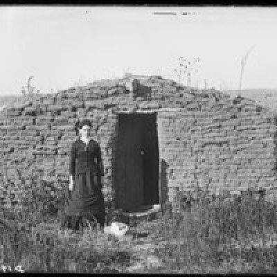a woman in front of her sod home