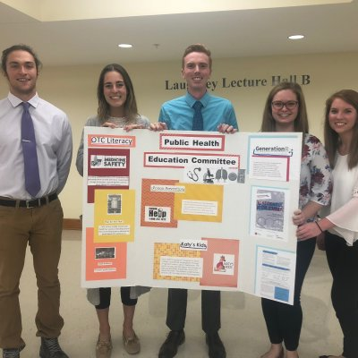 Students with a public health education poster