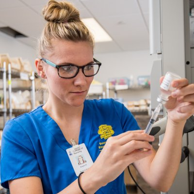 Nursing student is filling a needle with medicine