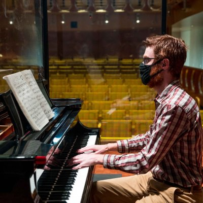 Student wearing a mask and playing a piano.