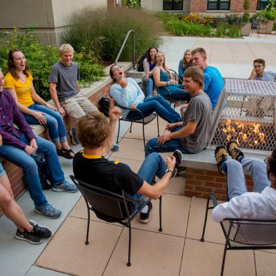 Students sitting around a firepit.
