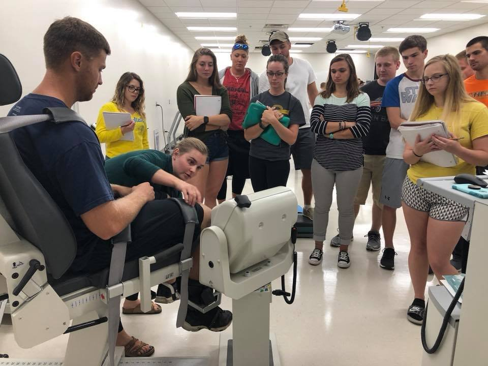 Students gathered around man sitting in biodex chair with instructor teaching.