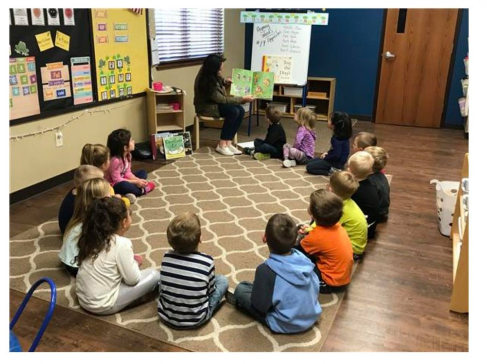 Teacher reads book to group of young students sitting in a circle on the floor.