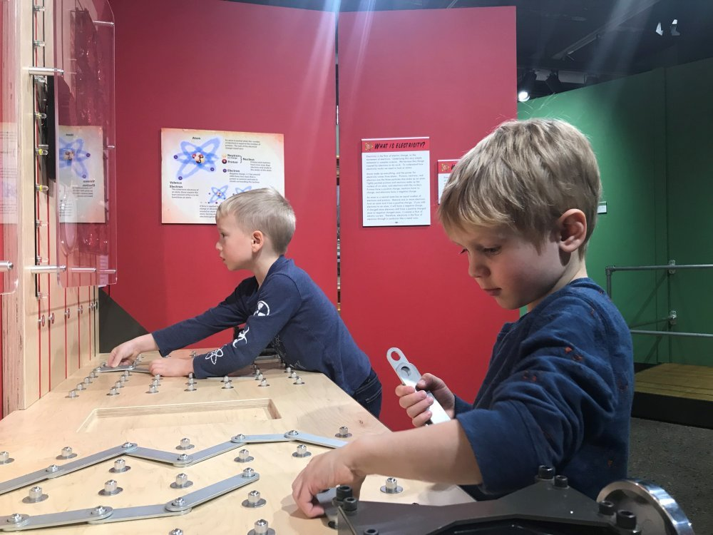 Two boys play with an interactive exhibit piece.