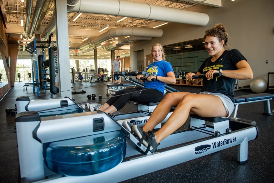 Students using rowing machine in wellness center