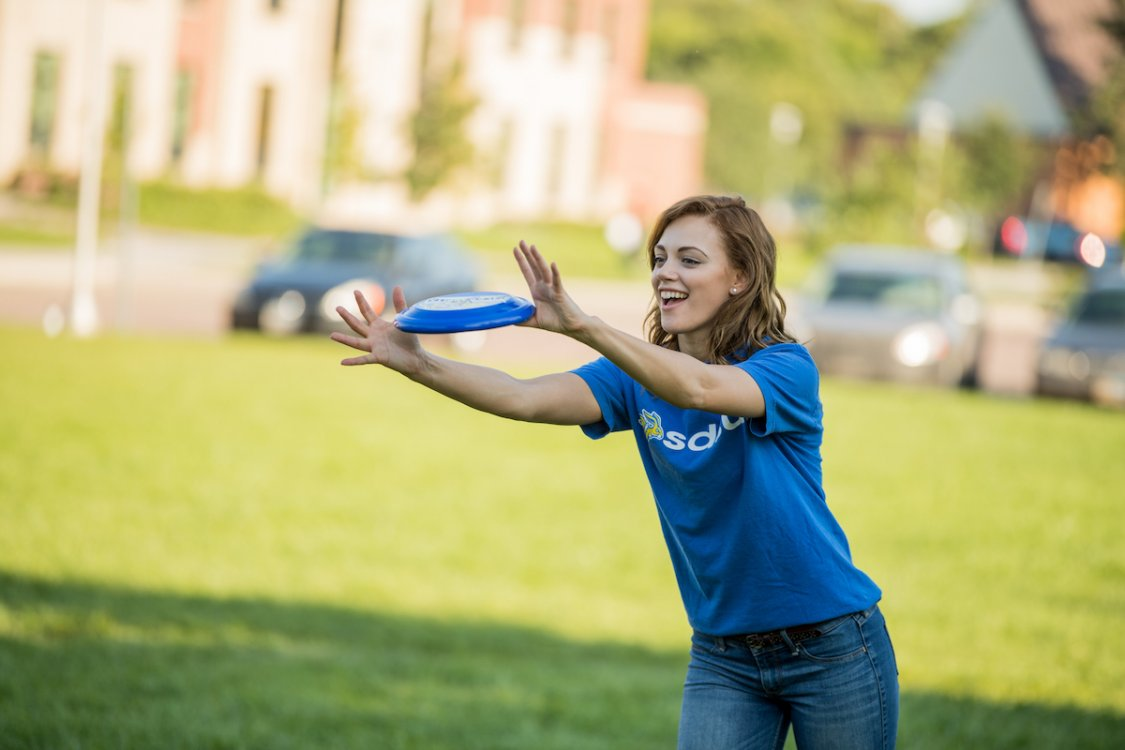 Student plays frisbee on campus.
