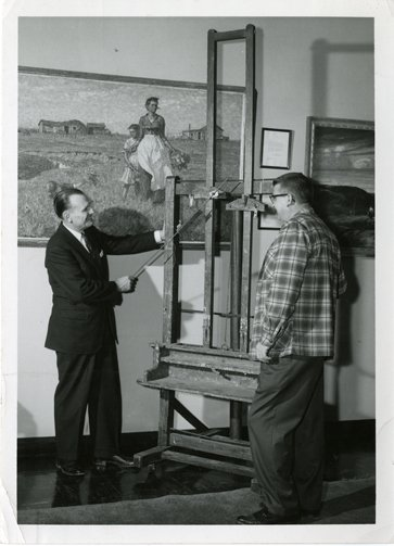 South Dakota State University President Hilton M. Briggs and Pugsley Union Manager Harlan R. Olson examine Harvey Dunn's easel on display in the Pugsley Student Union.