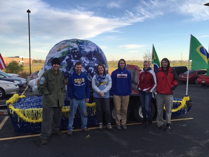 2016-2017 Geography Cub officers standing in front of their Hobo Day parade float