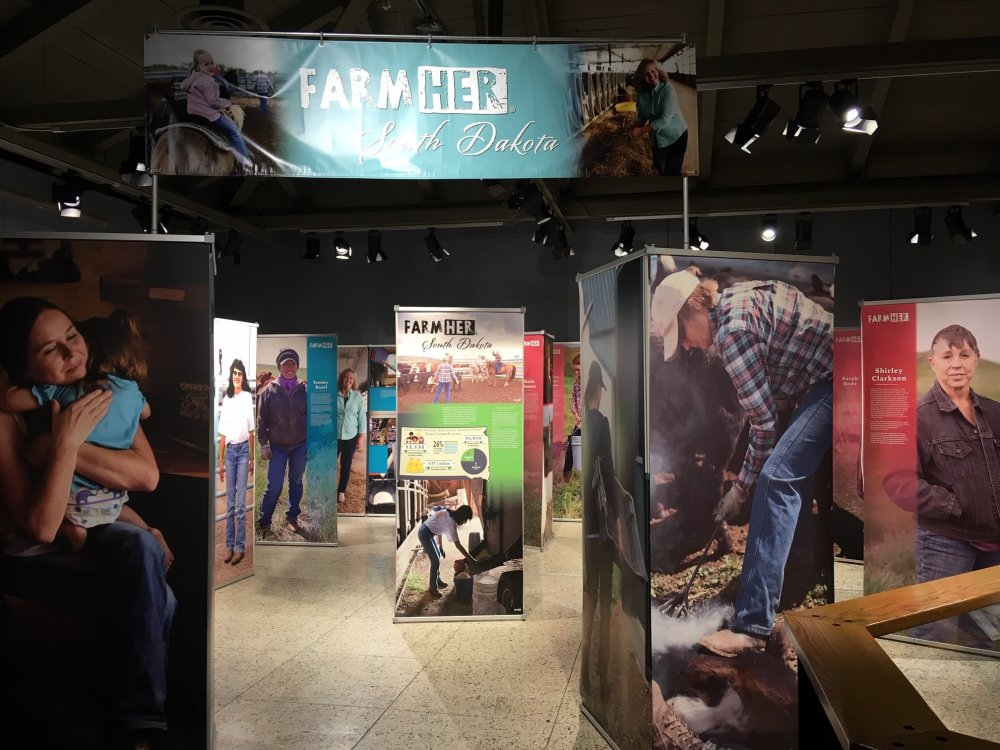 Farm:Her exhibit opening panels and banner, with producer profiles in the background.