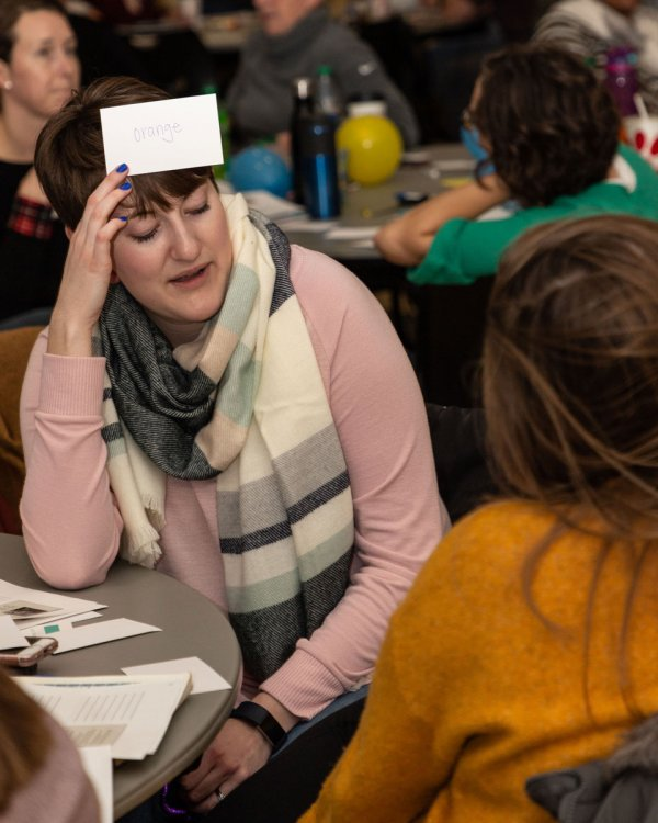 Holly Kelly tries to guess the word on the index card she holds on her forehead based on clues from her partner
