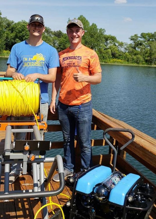 two students standing on dock at Dakota Nature Park with the drone