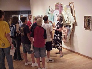 Museum volunteer discussing a piece of artwork to a group of visitors