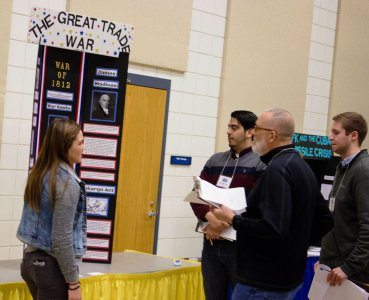"""NHD in SD Judges speaking with a student about her exhibit board titled, ""The Great Trade War."""""