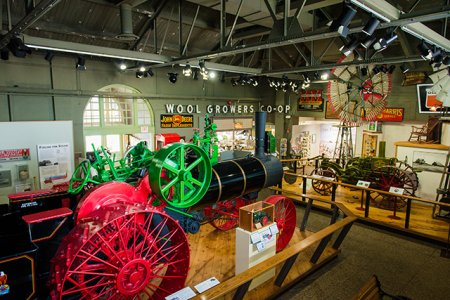 Image of museum interior. Large 65 horsepower Case Steam Traction Engine located in center of gallery.