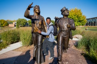 Student standing in between the Weary Wil and Dirty Lil Hobo Day Statues