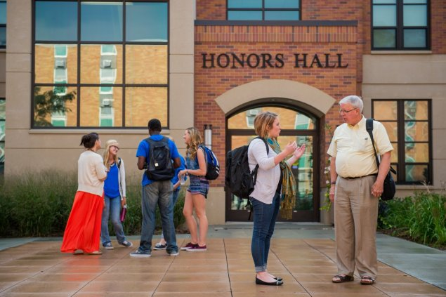 faculty and students talking in the courtyard of the Honors Hall building
