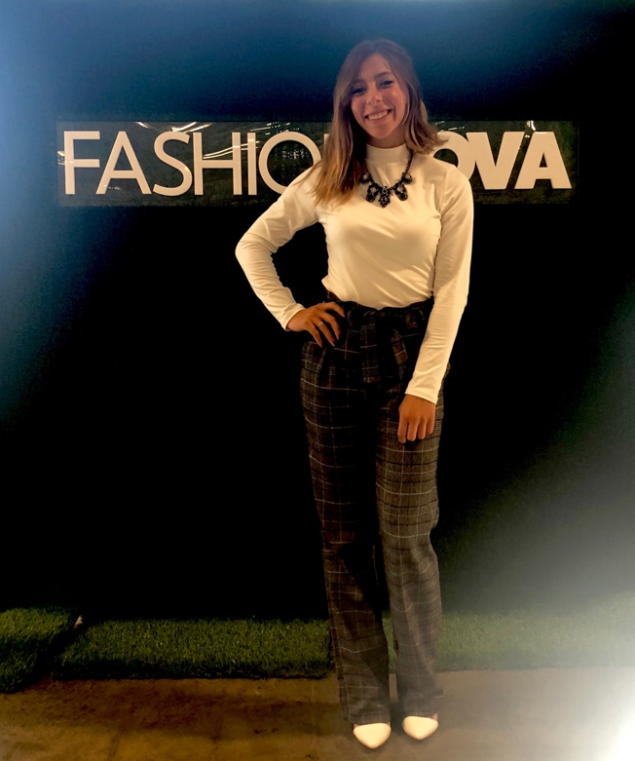 Dana Chavez poses in front of Fashion Nova sign.