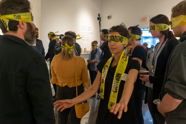 People blindfolded by police caution tape