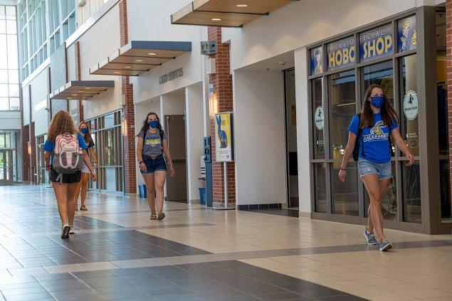 SDSU Students wearing masks and walking on University Student Union Main Street.