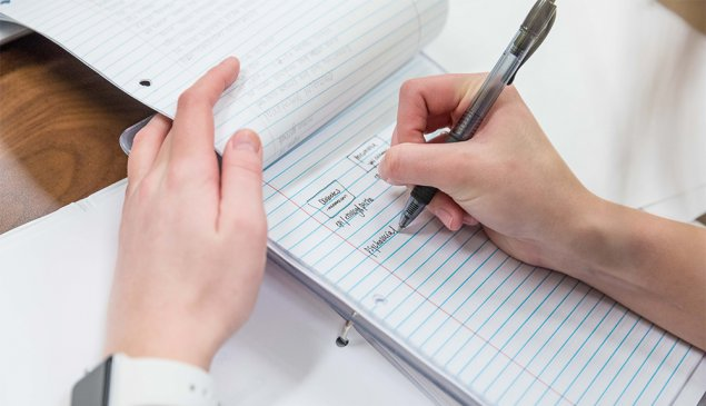 close up image of hands and a notebook