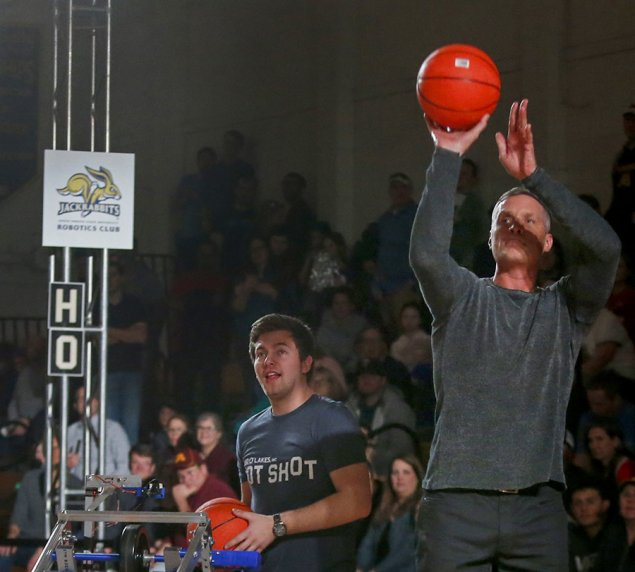 Former collegiate and professional basketball standout Christian Laettner shoots baskets against the South Dakota State Robotics team member Josh Gross at Land O'Lakes Bot Shot Sunday in Minneapolis.