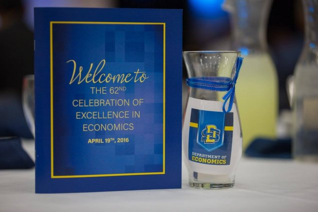 Welcome to the 62nd Celebration of Excellence in Economics April 19, 2016 banquet photo of table centerpieces - vase and program