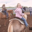 Young girls riding horses on a ranch.